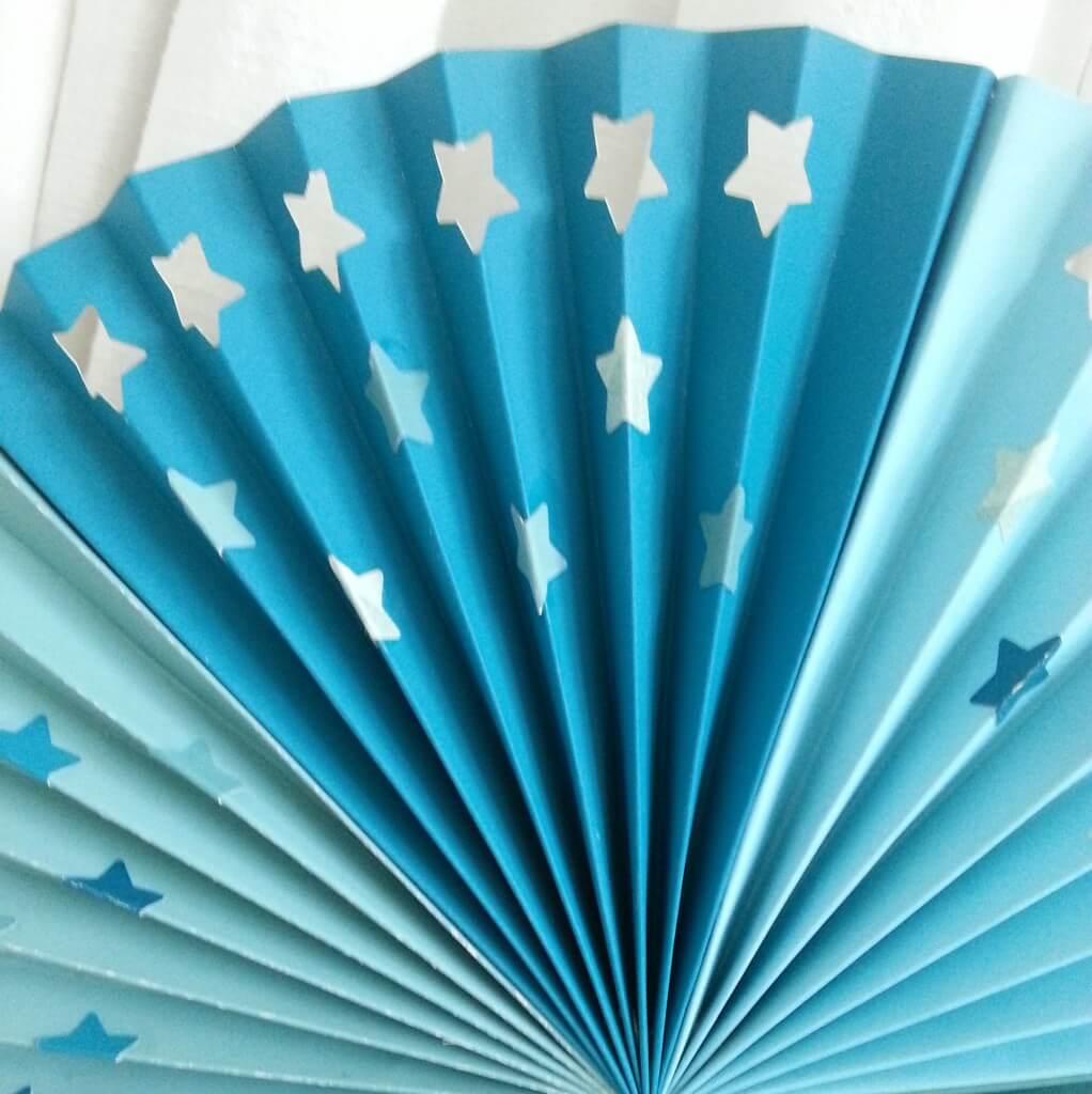 Een zelfgemaakte papieren waaier met sterren voor de kinderkamer