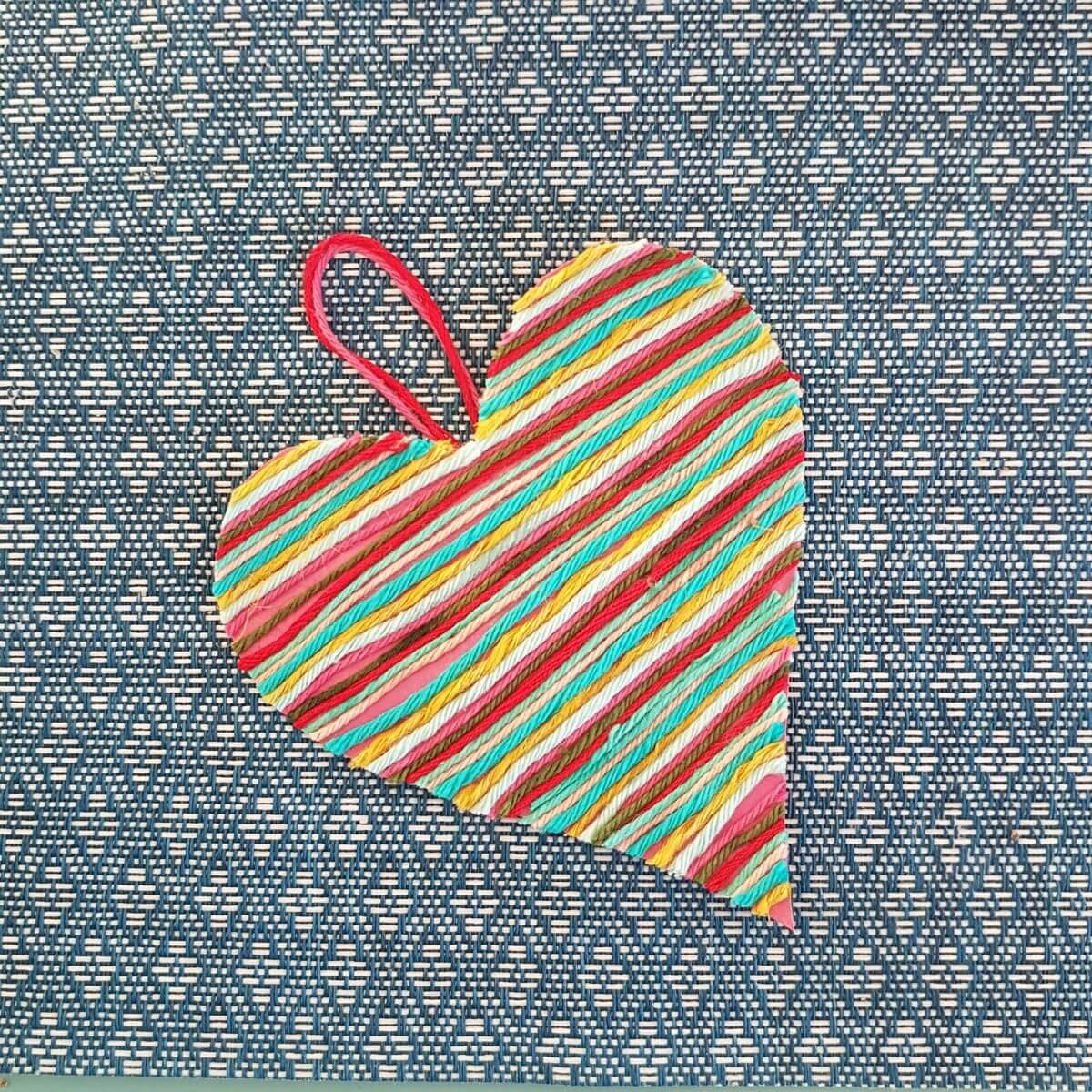 Knutselen voor Valentijnsdag: hartjes van wol plakken op papier