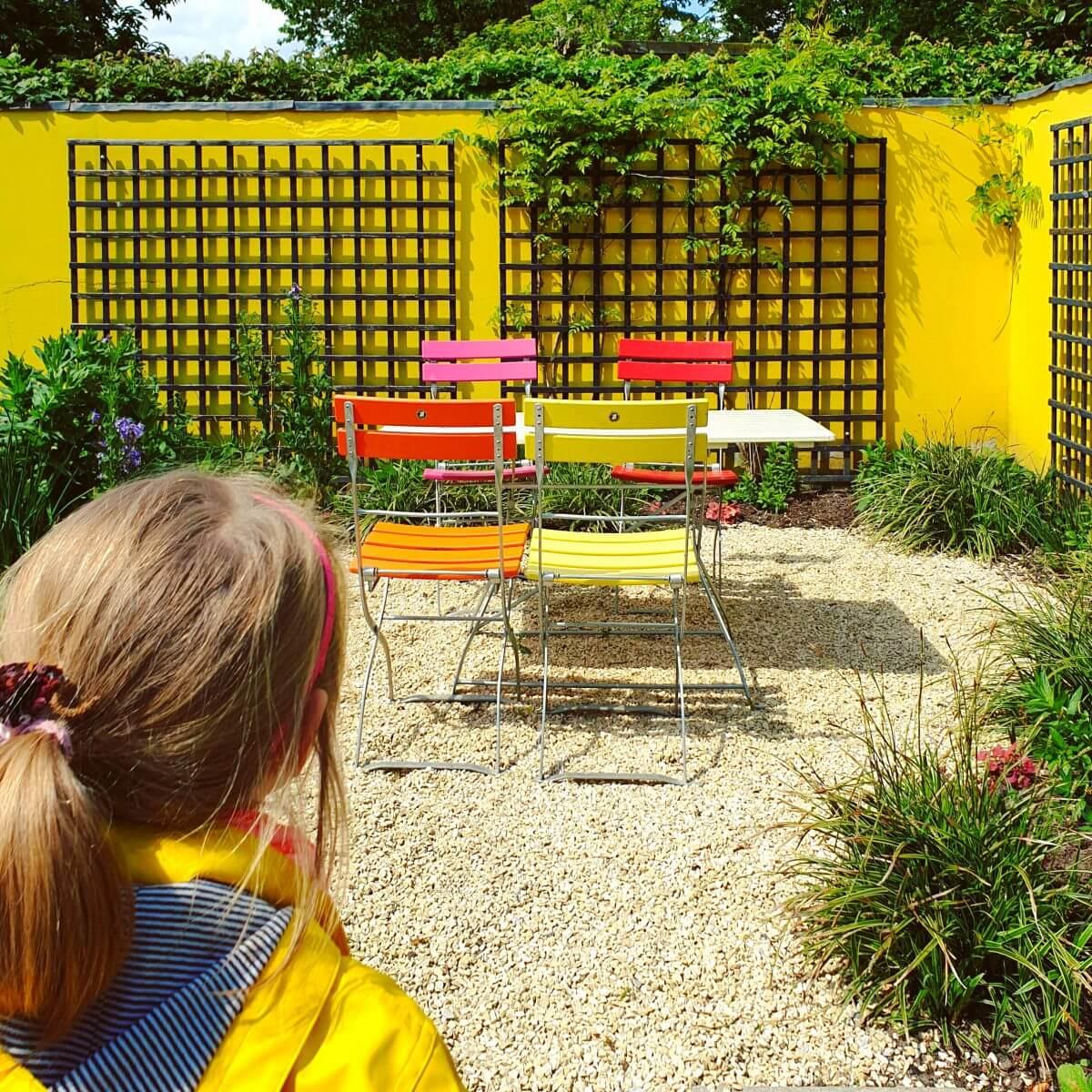 kleur in een kindvriendelijke tuin met een geverfde muur, schutting, tuinhuisje of schuur