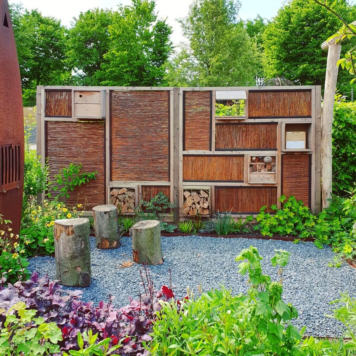 kindvriendelijke tuin met schutting met insectenhotel in de schutting