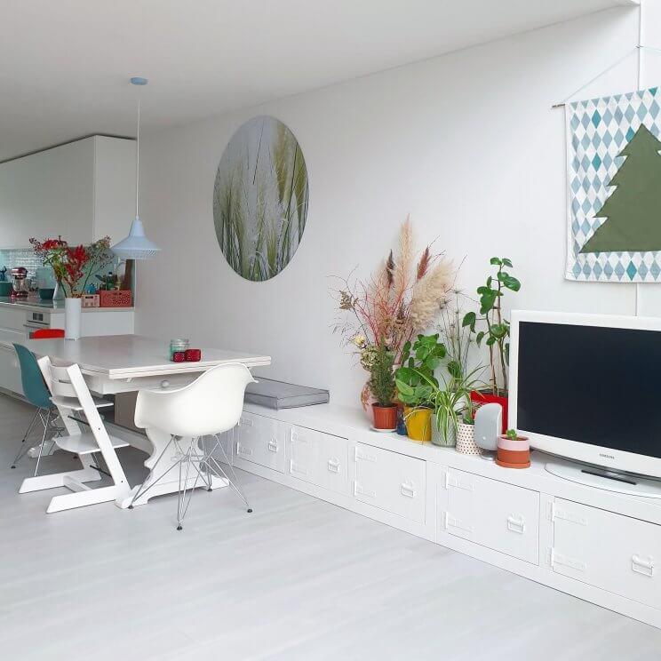 Binnenkijker: kleurrijke woonkamer met witte basis plus groen en vintage. Een van onze beste aankopen: het dressoir en eettafelbank in één, met bijpassend zitkussen. Doordat het vanaf de keuken bijna de hele muur beslaat, geeft het rust in de woonkamer. Bovendien benadrukt het aan de tuinkant de hoge vide.
