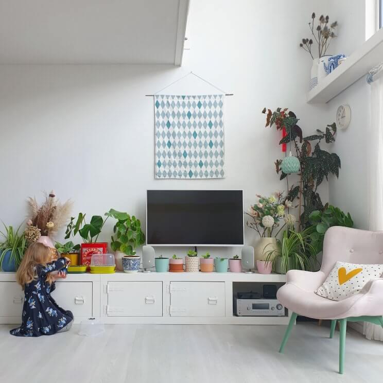 Binnenkijker: kleurrijke woonkamer met witte basis plus groen en vintage. Door het lange dressoir wordt de hoogte van de vide juist benadrukt. Door alle planten op het dressoir, is de televisie niet al te opvallend aanwezig.
