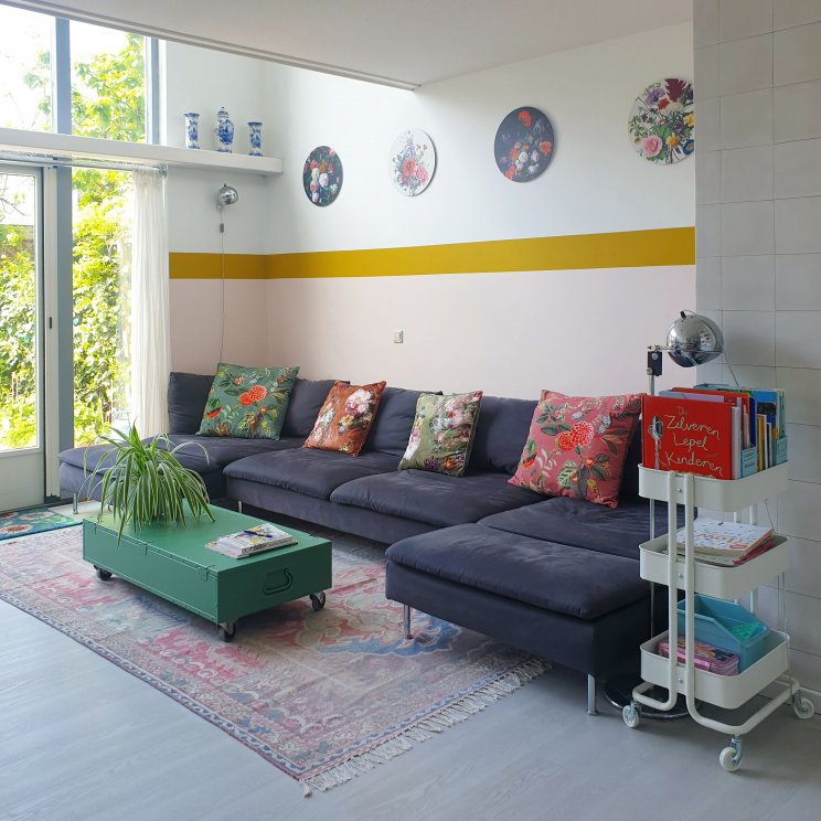 Binnenkijker: kleurrijke woonkamer met witte basis plus groen en vintage. De kleurrijke zithoek is veel warmer dan de rest van de woonkamer, waar de witte basis dominant is. Door ook hier groen toe te voegen, past het toch bij de rest van de woonkamer. We verfden de salontafel groen en zochten kussens met een botanische prints uit, die passen bij de muurdecoratie.