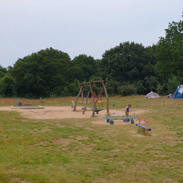 Huttopia de Roos: review van kindvriendelijke natuur camping in Overijssel. Er zijn veel verschillende speeltuinen, dit is de speeltuin naast plek 162. Er is onder meer een gewone schommel, nestschommel, waterpomp, zandbak, wipwap en ronddraaiende fietsjes.
