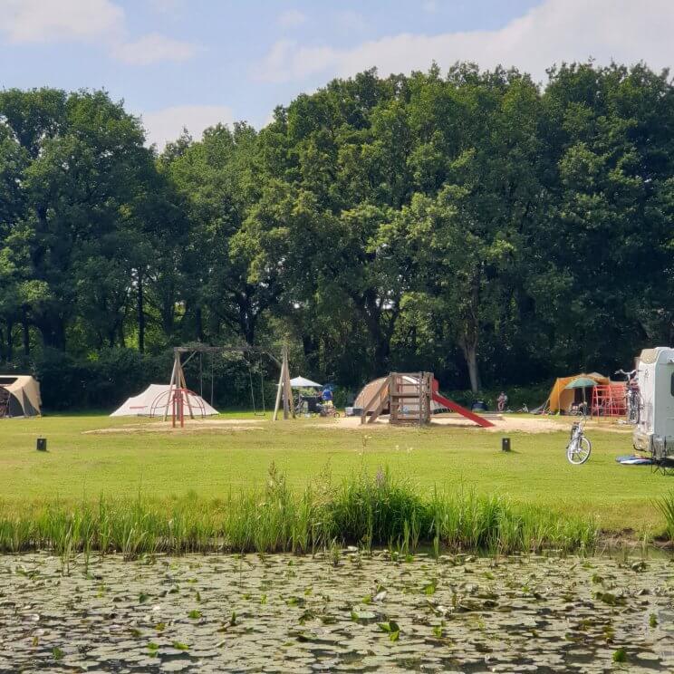 Huttopia de Roos: review van kindvriendelijke natuur camping in Overijssel. Er zijn veel verschillende speeltuinen, dit is de speeltuin bij plek 107. Er is onder meer een schommel, klimrek en glijbaantje. Kleine meis en haar vriendinnen gingen er heen als wij op het terras aan de andere kant van het water zaten.
