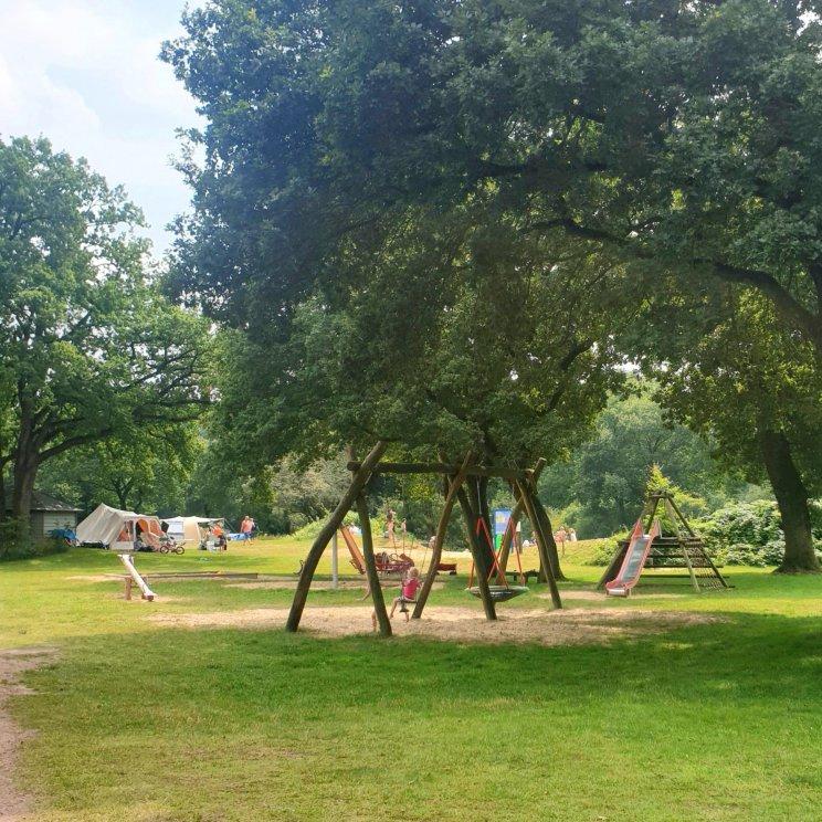 Huttopia de Roos: review van kindvriendelijke natuur camping in Overijssel. Er zijn veel verschillende speeltuinen, dit is de speeltuin naast het strandje, bij plek 14. Er is onder meer een gewone schommel en een nestschommel, een glijbaan, een wipwap en een zandbak.