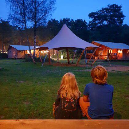 Kamperen met kinderen: idyllische kindvriendelijke campings in Nederland. De safaritenten glamping Landal Gooise Heide liggen midden in het bos. Wij verbleven in de 4-6-persoons safaritent. Deze tent heeft twee slaapkamers, een met een 2-persoonsbed en een mettwee stapelbedden. De woonkamer heeft een grote tafel, zithoek, keuken en veel ruimte. Daarnaast heb je een eigen badkamer. Buiten op de veranda zijn zowel een picknicktafel als een loungehoek.Fijn voor hondenliefhebbers: je mag je hond meenemen. Sommige safaritenten zijn ook speciaal voor honden uitgerust, bijvoorbeeld met een bench en bakken.