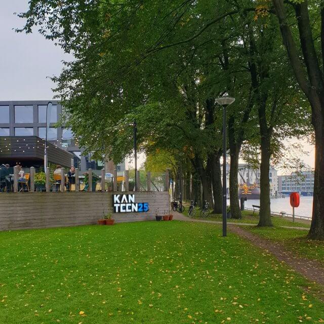 Kanteen25 Amsterdam: duurzaam restaurant met stoere speelruimte op Marineterrein, leuk voor kinderen en tieners. Het terras van Kanteen25 is kortgeleden gekozen tot het mooiste terras van Amsterdam. Geen wonder: het ligt aan het water van de Dijksgracht.Vanaf het terras heb je daarnaast uitzicht op Nemo en het Scheepvaartmuseum. Maar het ligt ook in het groen, bij mooi weer staan er extra biertafels en zitzakken in het gras.